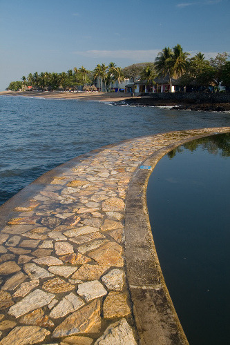 A rock path separates the sea from a salt water pool in El Salvador