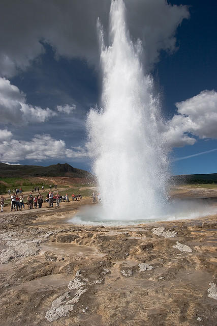 Tourists watching Strokkur Geyser in full eruption, Iceland